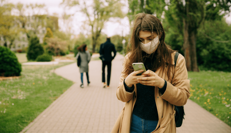 woman wearing mask using smartphone